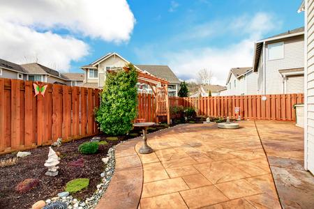 Photo pour Fenced backyard with concrete tile floor deck and decorated flower bed - image libre de droit
