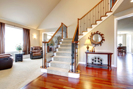Foto de View of hardwood hallway with staircase and  living room with leather armchairs and table - Imagen libre de derechos