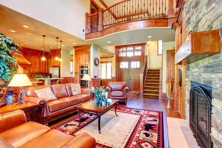Luxury living room with stone wall trim and fireplace Room furnished with rich leather furniture set and coffee table View of balcony loft