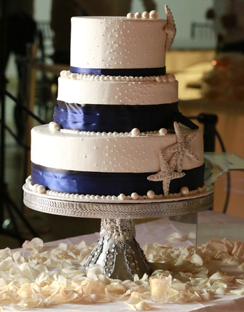 Three level wedding cake decorated with tasty pearls and sea stars