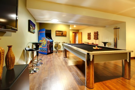 Photo for Fun play room home interior  Basement room without windows with pool table, TV, games  - Royalty Free Image