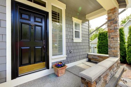 Foto de Grey house exterior with black door and stone wall. - Imagen libre de derechos