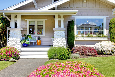 Photo for Entrance porch with stone column trim. View of flower bed with blooming bushes - Royalty Free Image
