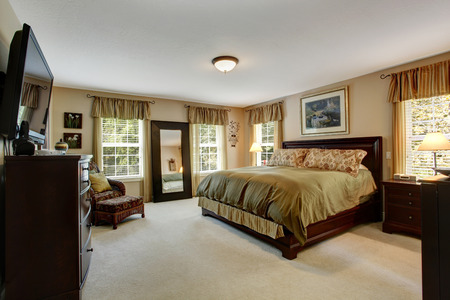 Cozy bedroom interior with carpet floor and wooden furniture set.  Room in olive olive colors