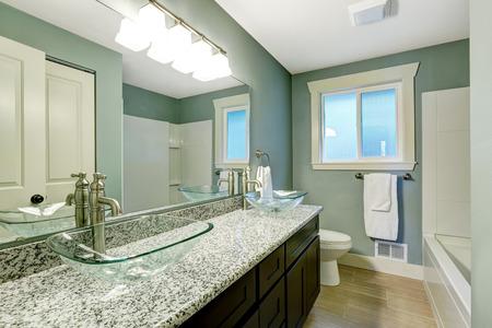 Foto de Modern bathroom interior with window. View of wooden vanity cabinet with granite counter top and glass vessel sinks - Imagen libre de derechos