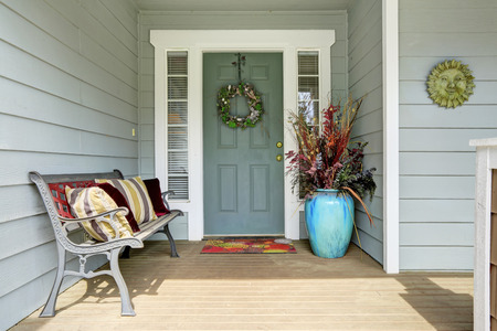 Photo for Entrance porch decorated with antique bench, big flower pot with dry branches - Royalty Free Image
