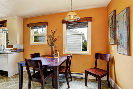 Dining area in old house. Peach wall blend with dark brown table set