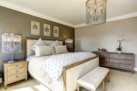Photo pour Luxury bedroom interior with carved wood bed, dresser and nightstands - image libre de droit