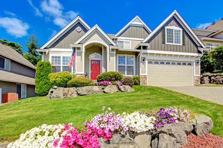 Foto de Grey house exterior with entrance porch and red door. Beautiful front yard landscape with vivid flower and stones - Imagen libre de derechos