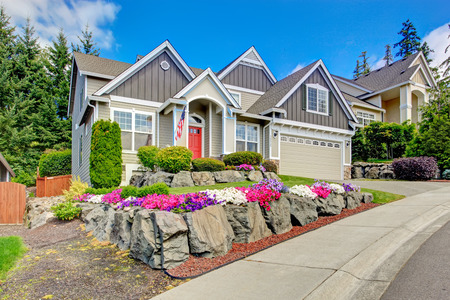 Photo pour Grey house exterior with entrance porch and red door. Beautiful front yard landscape with vivid flower and stones - image libre de droit