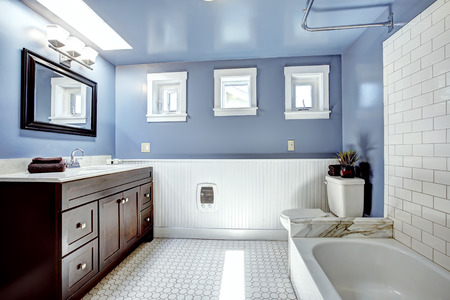 Beautiful lavender bathroom with white wall trim . Vanity cabinet with drawers and mirror. White bath tub with tile wall trim