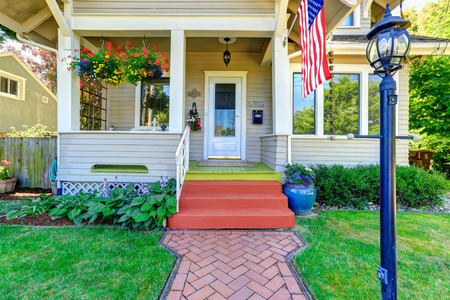 Photo for Classic american house entrance porch, decorated with hanging flower pots. Tile brick walkway - Royalty Free Image