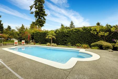 Backyard with beautiful swimming pool, deck chairs. Real estate in Federal Way, WA