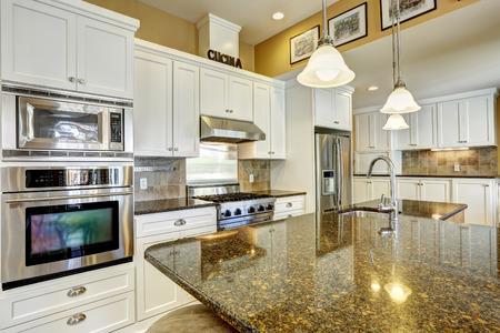 Foto de Bright kitchen room with granite tops, kitchen island and white cabinets - Imagen libre de derechos