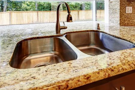 Foto de Kitchen cabinet with double steel sink and granite counter top. Close up view - Imagen libre de derechos