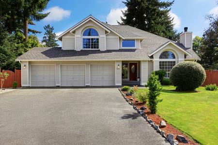 Foto de Luxury house exterior with tile roof. House with three car garage and front yard landscape - Imagen libre de derechos