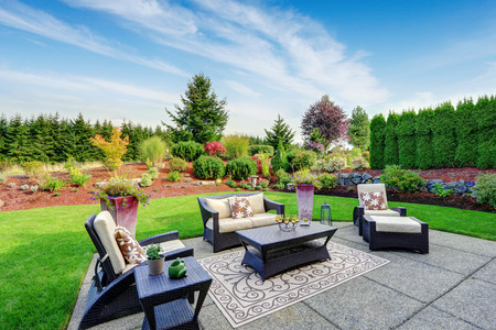 Foto de Impressive backyard landscape design. Cozy patio area with settees and table - Imagen libre de derechos