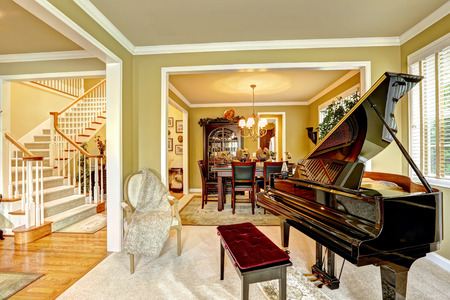Cozy family room interior in luxury house. Room with grand piano. Dining area and white staircase