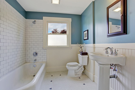 Photo for Bathroom interior with blue wall and white plank panel trim. Bath tub with tile wall trim. - Royalty Free Image