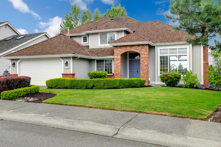Photo pour Classic house exterior with brick trimmed entrance porch, green lawn and trimmed hedges - image libre de droit