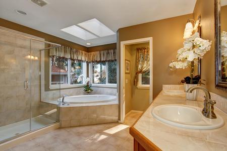Large elegant master bathroom with shower, and big bath tub.