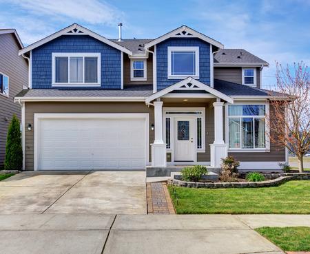 Foto de Large blue and gray home with white trim, also a driveway. - Imagen libre de derechos