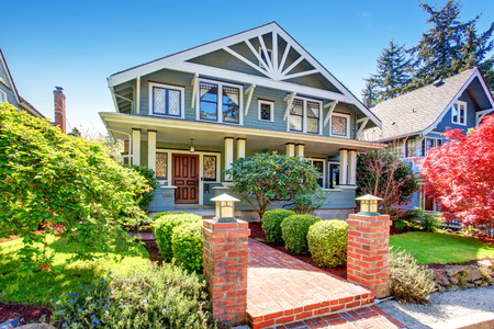 Foto de Large luxury blue craftsman classic American house exterior. View of brick walkway decorated with trimmed hedges. - Imagen libre de derechos