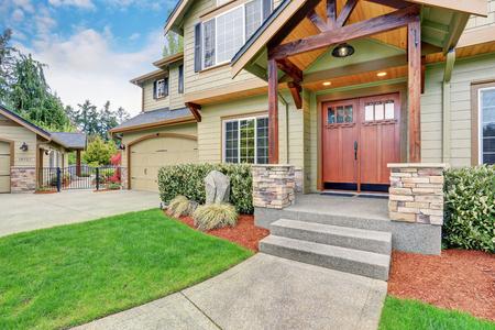 Foto de View of house entrance with concrete walkway, stone column trim and double doors. - Imagen libre de derechos