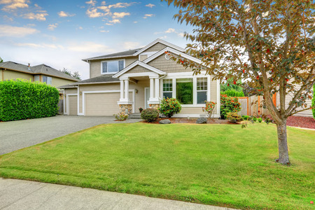 Foto de Neat beige home with two garage spaces and well kept front garden. Northwest, USA - Imagen libre de derechos