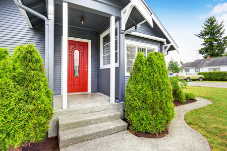 Photo for Classic American house exterior with siding trim, red entry door and concrete floor porch. Northwest, USA - Royalty Free Image