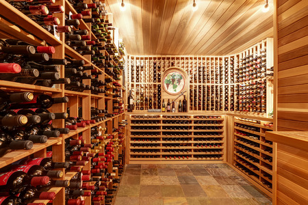 Foto de Bright home wine cellar with wooden storage units and arch with bottles. Northwest, USA - Imagen libre de derechos
