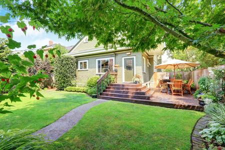 Photo pour Backyard area with walkout deck, patio table set and well kept lawn. Northwest, USA - image libre de droit