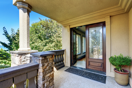 Photo for Luxury house exterior. Entrance column porch with railings and rug Open front door. Northwest, USA - Royalty Free Image