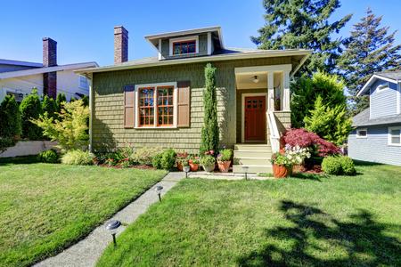 Photo pour Small green American craftsman house exterior with entrance column porch. Northwest, USA - image libre de droit