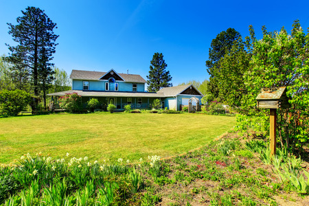 Photo pour Beautiful curb appeal of large blue  country house. Well kept lawn with flower beds. Northwest, USA - image libre de droit