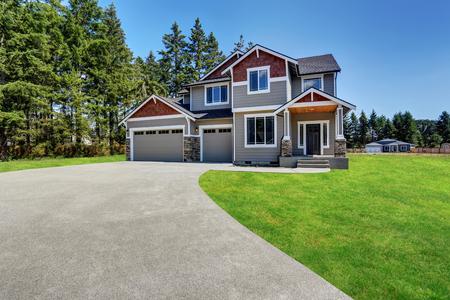 Foto de Classic large craftsman American house exterior with rocks trim, garage and concrete floor porch. Also well kept lawn around. Northwest, USA. - Imagen libre de derechos