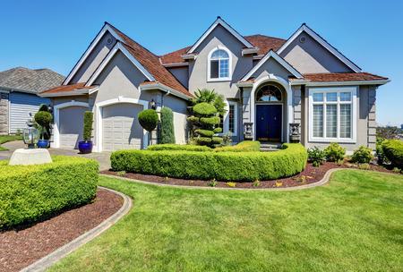 Foto de Luxury residential house with perfectly kept front garden and blue sky background. Northwest, USA - Imagen libre de derechos