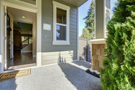 Foto de Entrance porch of American gray house with open front door with welcome mat on a sunny day. Northwest, USA - Imagen libre de derechos