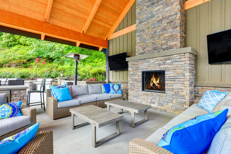 Photo pour Inviting interior of covered patio area  in Tacoma Lawn Tennis Club. Stone fireplace, wicker furniture with beige cushions and bright blue pillows. Northwest, USA - image libre de droit