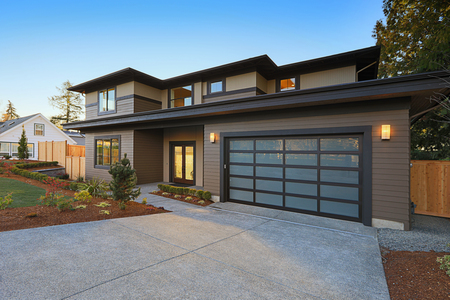 Photo for New construction home exterior with contemporary house plan  features low slope roof, brown siding and glass garage door. Northwest, USA - Royalty Free Image