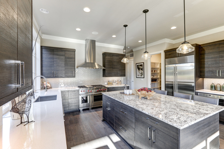 Photo pour Modern gray kitchen features dark gray flat front cabinets paired with white quartz countertops and a glossy gray linear tile backsplash. Bar style kitchen island with granite counter. Northwest, USA  - image libre de droit