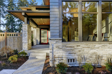 Photo pour Entrance of  Luxurious new construction home with blue siding and stone decor. Concrete walkway lead to long covered porch with modern glossy front door. Northwest, USA - image libre de droit