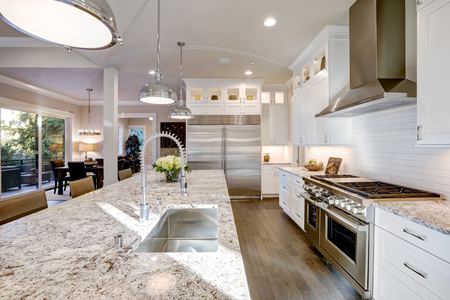 Photo pour White kitchen design features large bar style kitchen island with granite countertop illuminated by modern pendant lights. Stainless steel appliances framed by white shaker cabinets . Northwest, USA - image libre de droit