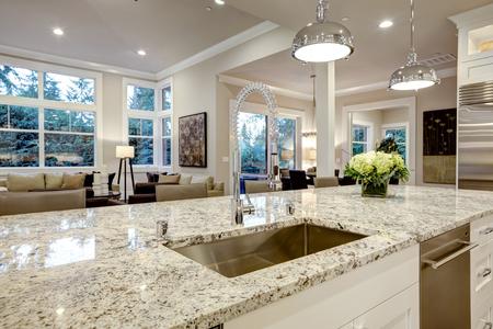 Foto de White kitchen design features large bar style kitchen island with granite countertop illuminated by modern pendant lights. Northwest, USA - Imagen libre de derechos