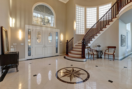 Photo for Stunning two story entry foyer with lots of space boasts marble mosaic tile floor, front door framed with arch window and sidelights, grand staircase with glossy wood curved banister. Northwest, USA - Royalty Free Image