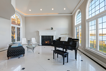 Luxury high ceiling living room features beige ivory walls framing large arched windows, traditional fireplace, black grand piano next to cozy sitting area atop glossy marble floor. Northwest, USA