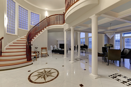Photo pour Stunning spacious entry foyer with columns boasts marble mosaic tile floor and grand staircase with glossy wood curved banister. The foyer flanked by formal dining room and living room. Northwest, USA - image libre de droit