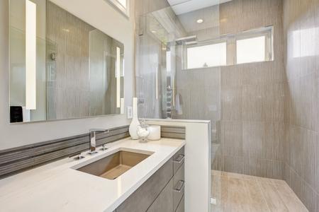 Foto de Contemporary bathroom features a dark vanity cabinet fitted with rectangular sink and walk-in shower. Northwest, USA - Imagen libre de derechos