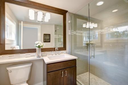 Foto de Modern bathroom features a dark vanity cabinet fitted with rectangular sink under a large full mirror and glass walk-in shower. Northwest, USA - Imagen libre de derechos