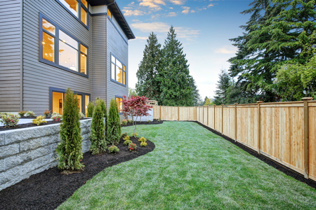 Foto de Luxurious contemporary three-story wood siding home exterior in Bellevue. Nice backyard landscape with well kept lawn, flower beds and wooden fence. Northwest, USA - Imagen libre de derechos